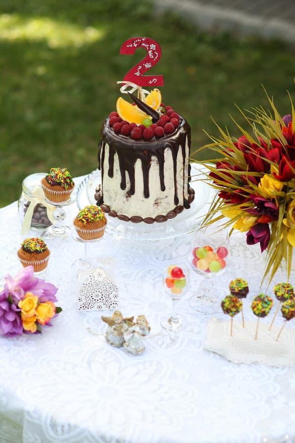 Uma tabela festiva decorada com o bolo de aniversário com flores e doces imagens de stock