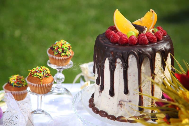 Uma tabela festiva decorada com o bolo de aniversário com flores e doces fotografia de stock royalty free