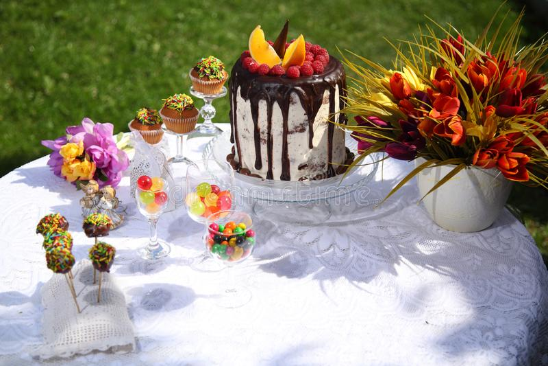 Uma tabela festiva decorada com o bolo de aniversário com flores e doces fotos de stock