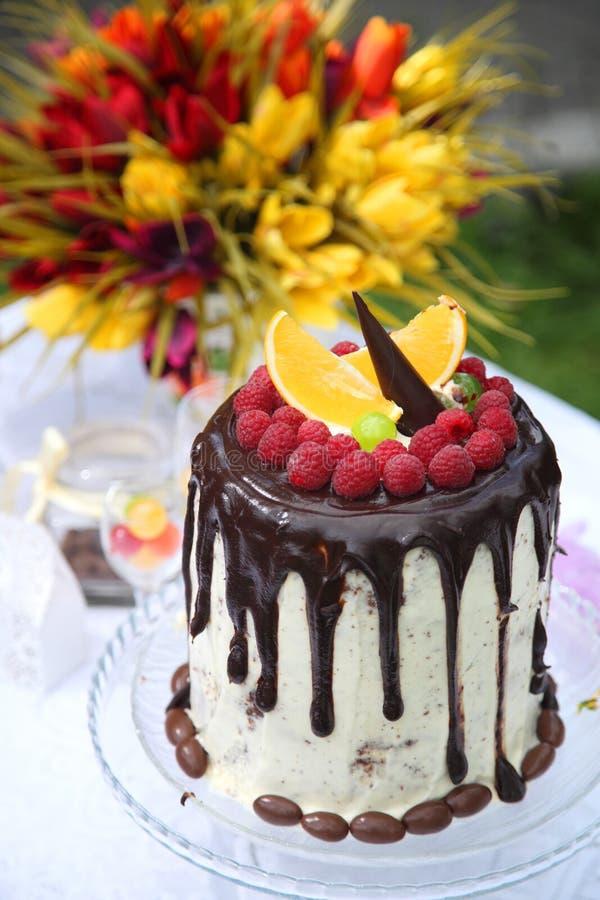 Uma tabela festiva decorada com o bolo de aniversário com flores e doces foto de stock