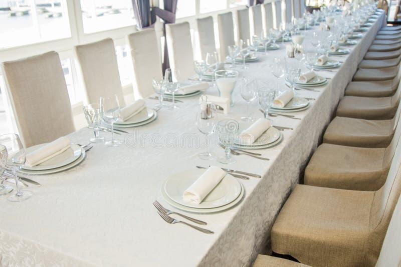 Uma tabela longa coberta com uma toalha de mesa branca com cutelaria e vidros foto de stock