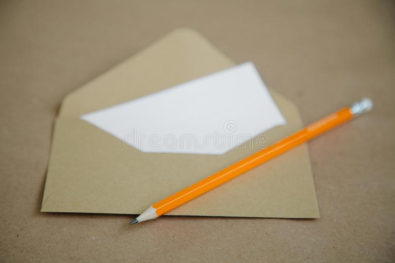 Uma tabela marrom do vintage e um envelope com um lápis amarelo fotos de stock