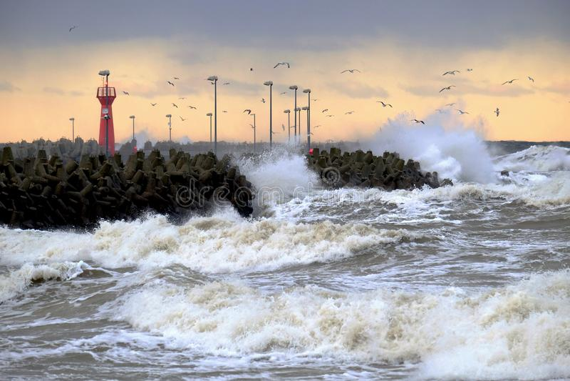 Uma tempestade do inverno na costa do mar Báltico, grandes ondas inunda sobre o quebra-mar portuário imagem de stock royalty free