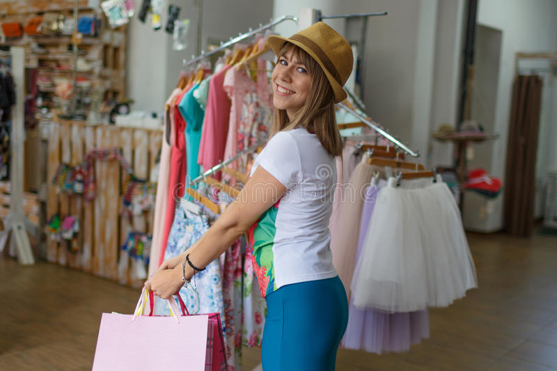 Uma terra arrendada shopaholic satisfeito suas compras na loja de roupa Uma jovem mulher de sorriso em um fundo borrado cópia imagem de stock royalty free