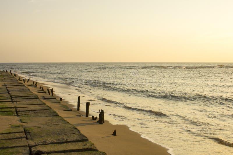 Uma terraplenagem concreta no fundo de um Sandy Beach e o mar sob um céu de nivelamento cinzento foto de stock