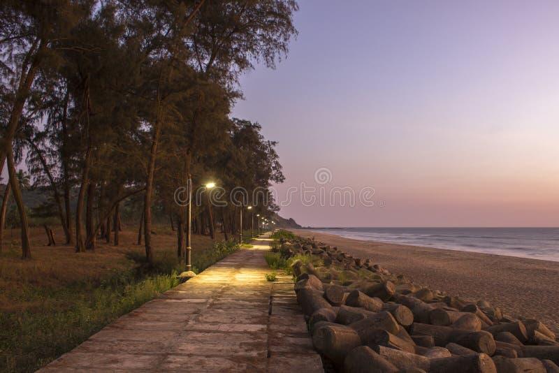 Uma terraplenagem de nivelamento com as lanternas de incandescência na costa de mar com um Sandy Beach e uma barreira do tsunami  foto de stock
