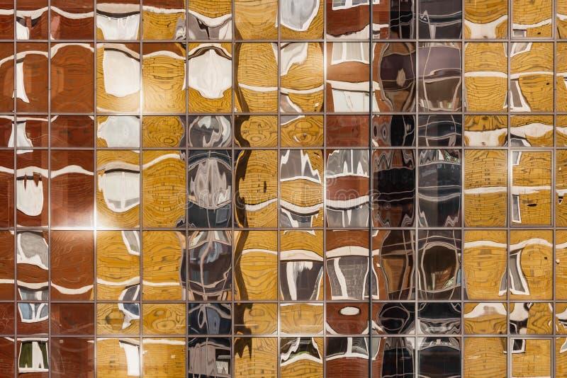 Uma textura horizontal bonita da peça de uma parede de vidro colorida com reflexões de uma construção moderna nova em amarelo e e fotos de stock