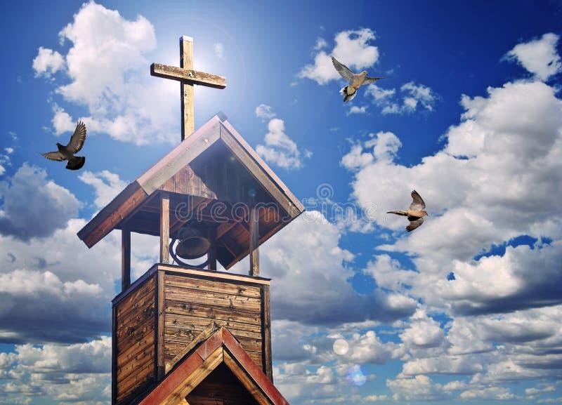 Uma torre de Bell com cruz, luz celestial e pombas foto de stock royalty free