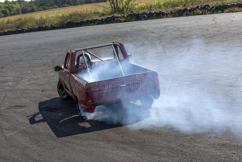 Uma tração que compete o camionete na ação com fumo cansa-se fotografia de stock