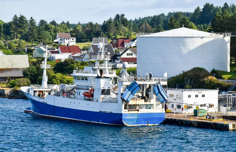 Uma traineira dos peixes azuis e brancos amarrou em um posto de gasolina no porto imagens de stock