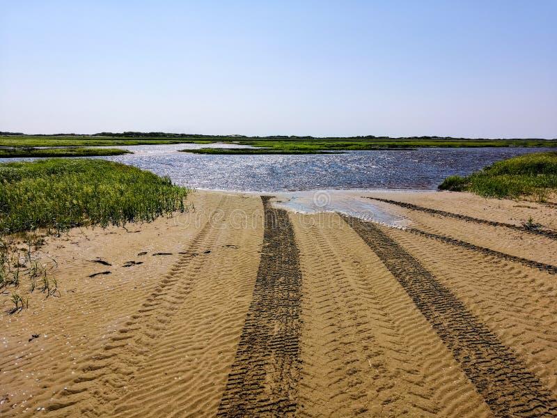 Uma trilha de vários tipos de veículos automotivos na areia aproxima um rio que precise de ser baixio, uma paisagem do verão do foto de stock