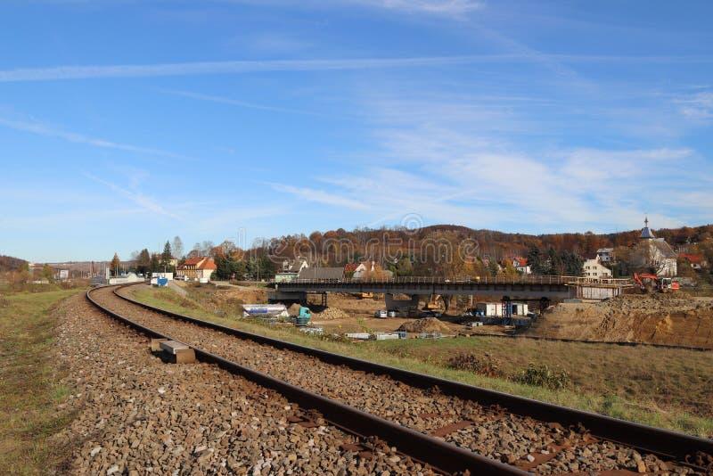 Uma trilha railway electrificada entre prados e campos de trigo verdes Construindo uma ponte em uma cidade pequena fotos de stock