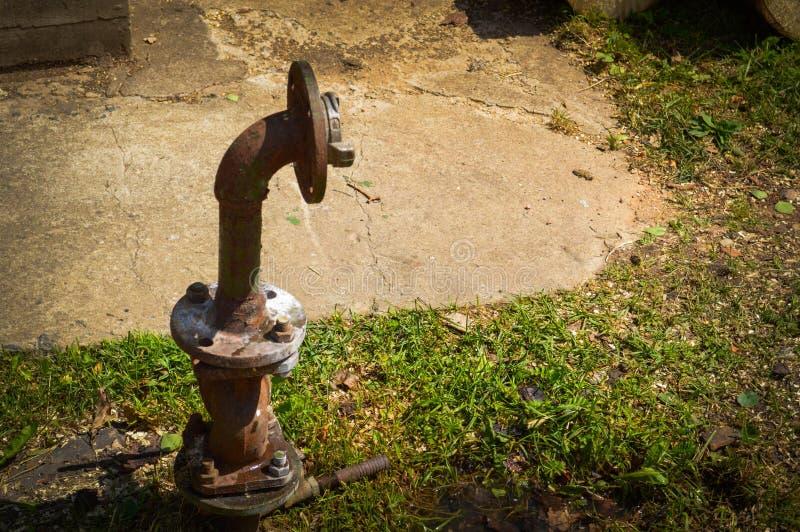 Uma tubulação de fonte industrial velha da água do corrosivo oxidado do ferro para a fonte de água com uma flange que move-se com imagem de stock