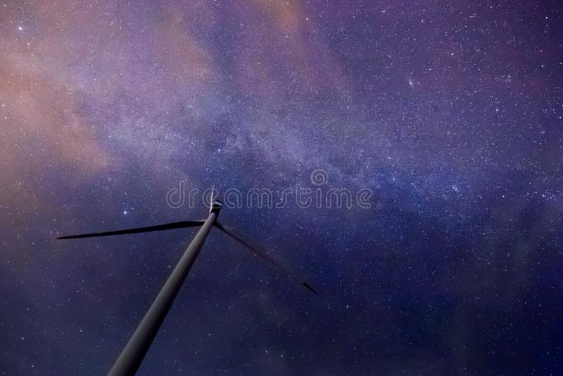 Uma turbina eólica com Via Látea bonita no fundo com as estrelas brilhantes sobre a terra lisa na meia-noite foto de stock