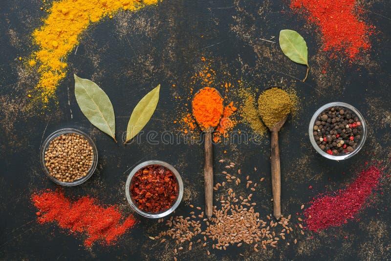 Uma variedade de fundo colorido das especiarias Especiarias em colheres de madeira em um fundo rústico escuro Vista de acima foto de stock