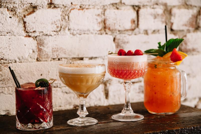 Uma variedade de quatro cocktail alcoólicos contra o backgr branco do tijolo foto de stock
