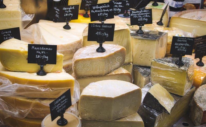 Uma variedade de queijo para a venda no supermercado fino contra foto de stock