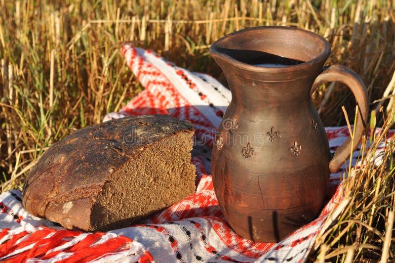 Uma vasilha de barro do leite e de um meio naco do pão de centeio imagem de stock royalty free