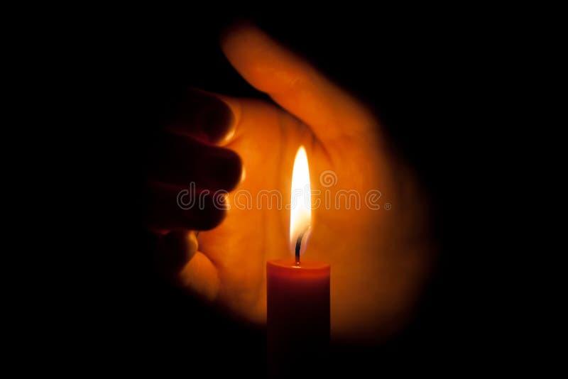 Uma vela ardente na noite, protegida pela mão de uma mulher Chama de vela que incandesce em um fundo escuro com espaço livre para fotografia de stock
