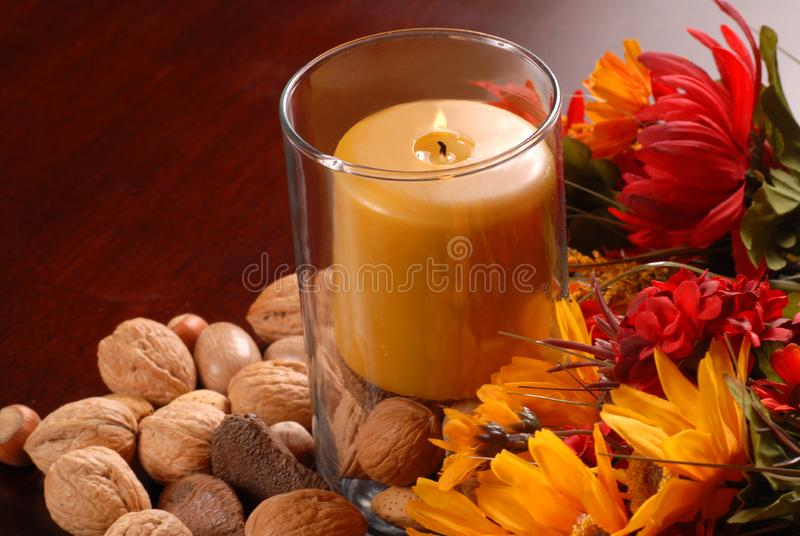 Uma vela em um ajuste do outono imagem de stock royalty free