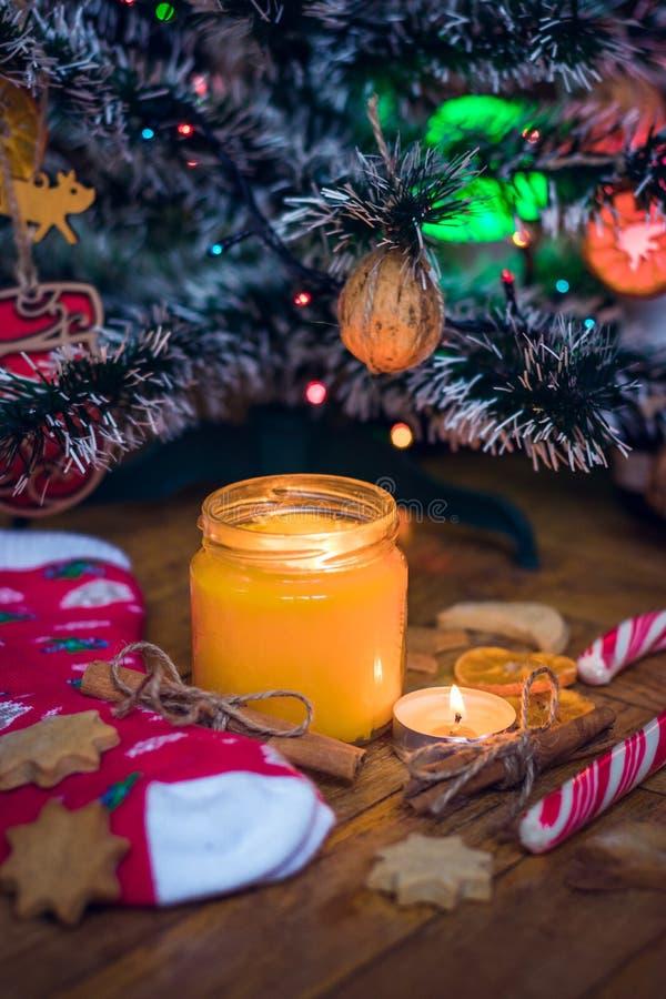 Uma vela está queimando-se sob a árvore de Natal, é próximo cookies, doces, peúgas de lãs e mitenes foto de stock