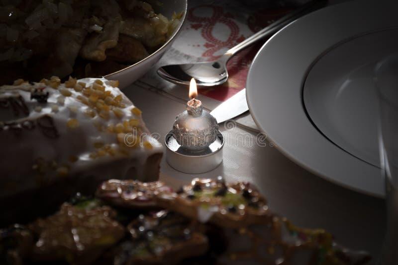 Uma vela iluminada do Natal em uma tabela ao lado do cooki colorido geado fotografia de stock