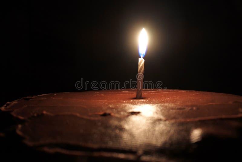 Uma vela no bolo de aniversário do chocolate fotos de stock