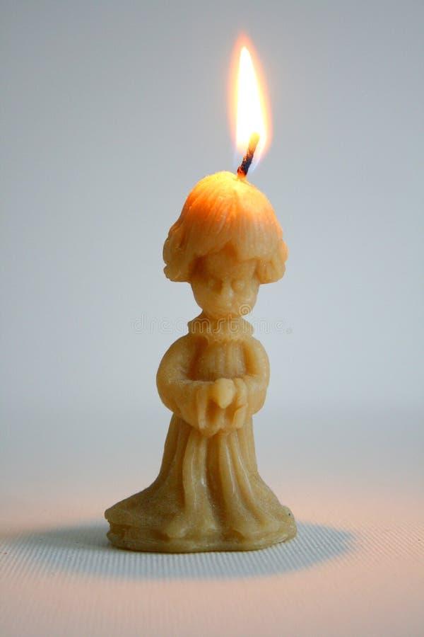 Uma vela sob a forma de rezar da criança foto de stock royalty free