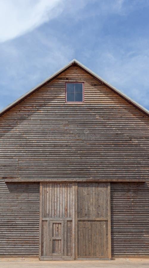 Uma vertente de madeira da exploração agrícola e um céu azul fotografia de stock