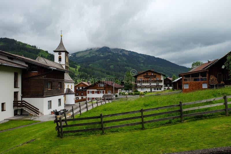 Uma vila austríaca pequena com casas típicas e uma igreja fotografia de stock