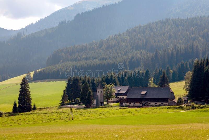 Uma vila austríaca pequena típica no pé das montanhas alpinas fotografia de stock