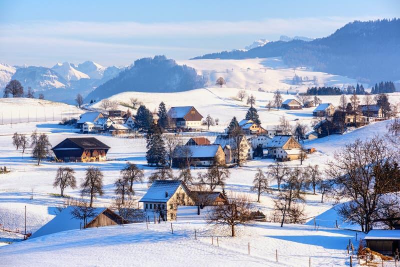 Uma vila coberto de neve em cumes suíços, Suíça, no tempo de inverno fotos de stock royalty free