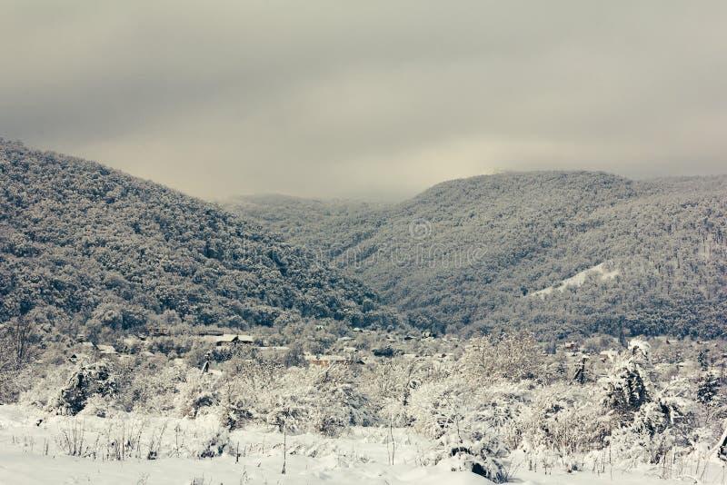 Uma vila nos montes dos montes nevado nebulosos cedo na manhã fotografia de stock royalty free