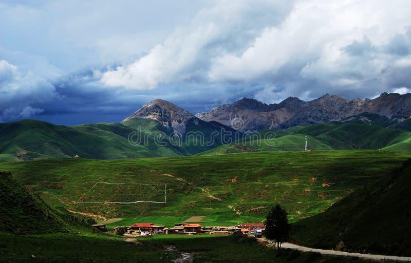 Uma vila pequena abaixo da montanha em Tibet fotos de stock
