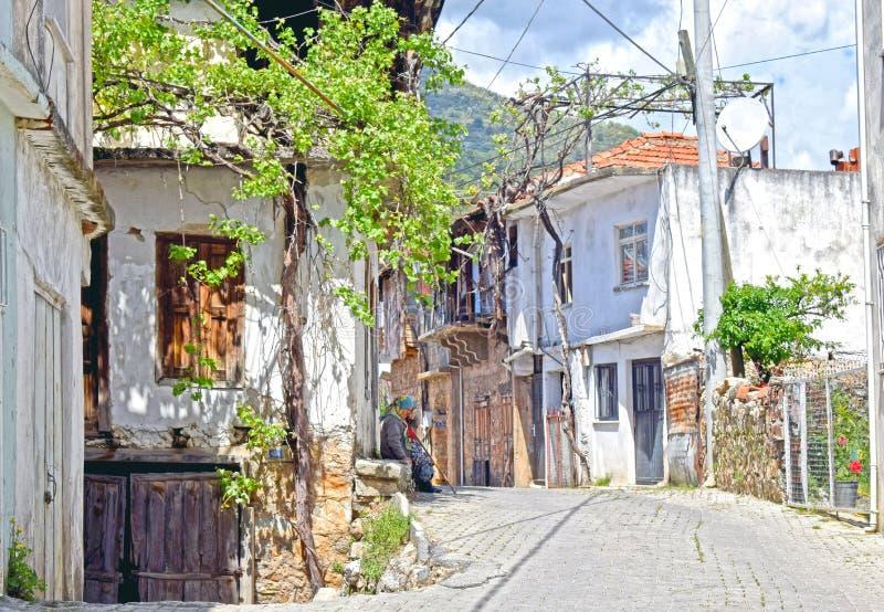 Uma vila turca típica com uma senhora que senta-se na etapa da porta foto de stock