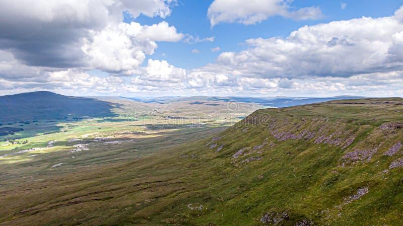 Uma vista aérea de um vale da montanha com inclinação, a noiva da estrada de ferro e escala verdes da cimeira da montanha no fund imagem de stock