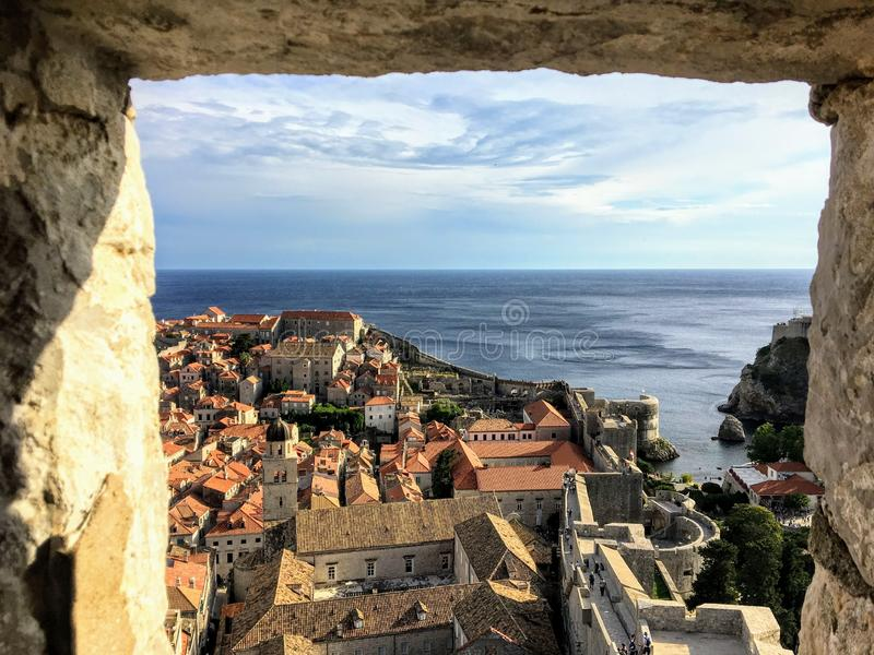 Uma vista através da janela de pedra da torre de Minceta ou da fortaleza que olha para fora na cidade e nas paredes velhas de Dub imagens de stock royalty free