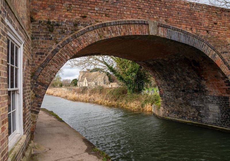 Uma vista através da ponte da casca de noz da igreja Stonehouse do St Cyr's na navegação restaurada da água de Stroud foto de stock royalty free