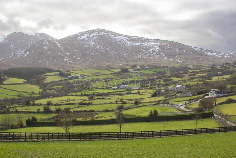 Uma vista através de um vale a uma da neve do splindid espanou picos das montanhas de Mourne no condado para baixo Irlanda do Nor imagem de stock