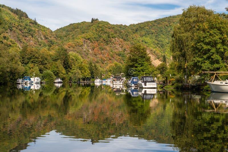 Uma vista bonita de um lago calmo entre os montes com os barcos amarrados à costa fotos de stock