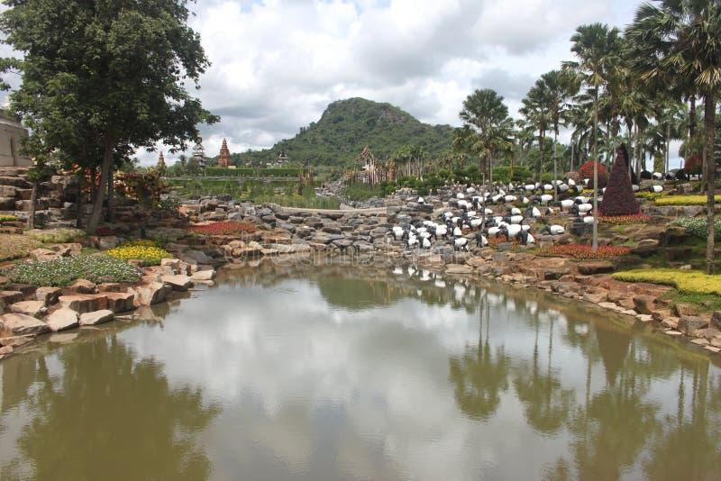 Uma vista bonita a um prado com lagoa e grama e árvores e pedras no jardim botânico tropical de Nong Nooch perto da cidade de Pat imagens de stock