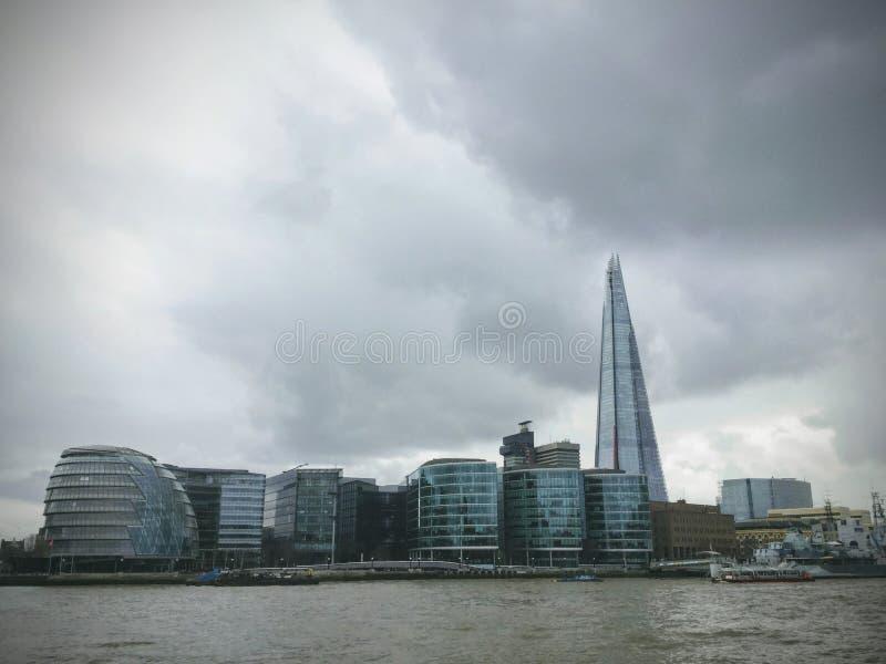 Uma vista da câmara municipal famosa de Londres do banco do rio Tamisa contra um céu nebuloso dramático fotografia de stock