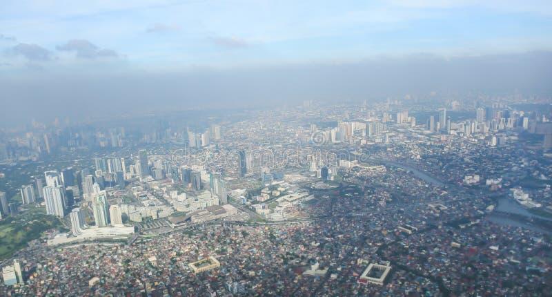 Uma vista da cidade de Manila através da janela do plano Foto impressa de um turista em voo sobre o capital imagem de stock