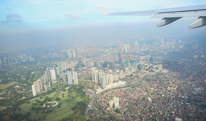 Uma vista da cidade de Manila através da janela do plano Foto impressa de um turista em voo sobre o capital imagens de stock royalty free