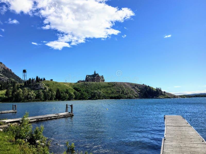 Uma vista da doca através de um lago bonito a um hotel majestoso apenas sobre o monte foto de stock royalty free