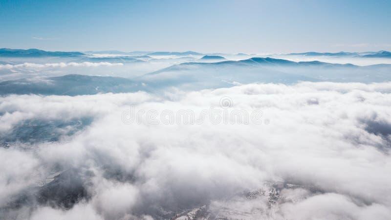 Uma vista da parte superior da montanha ao vale coberto com as nuvens com um céu azul claro em um dia ensolarado fotografia de stock