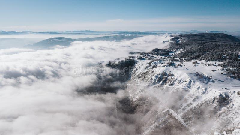 Uma vista da parte superior da montanha aos penhascos cobertos com a neve e ao vale do pinho com um céu azul claro em um dia enso fotos de stock royalty free