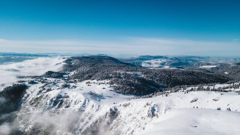 Uma vista da parte superior da montanha aos penhascos cobertos com a neve e ao vale do pinho com um céu azul claro em um dia enso imagem de stock