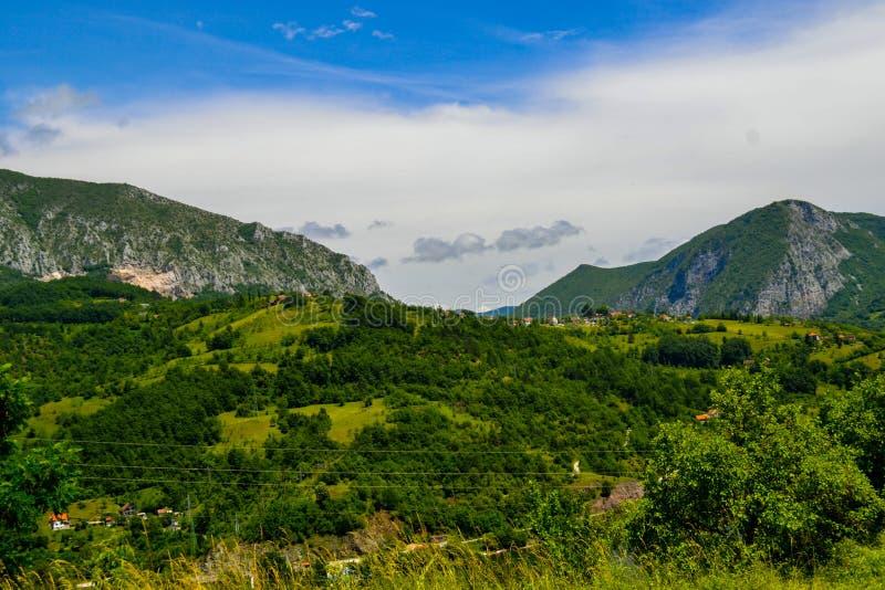 Uma vista das grandes montanhas acima do prado verde e o céu azul bonito da floresta A e um vestido no fundo fotos de stock royalty free