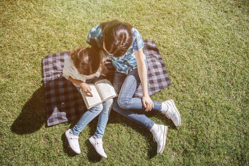 Uma vista de cima de onde a mãe e sua criança se estão sentando junto na cobertura e se estão olhando o livro Estão lendo-o imagens de stock royalty free